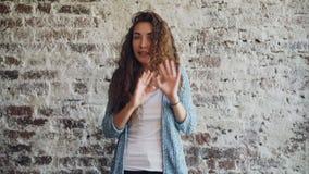 Stående av den ilskna unga kvinnan som talar och gör en gest uttrycka negativa sinnesrörelser som inomhus står med vindstil lager videofilmer