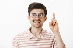 Stående av den intensiva allvarliga europeiska manliga läraren i runda exponeringsglas och att lyfta pekfingret i eureka eller, m Arkivfoto