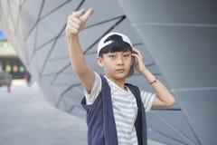 Stående av den kalla asiatiska ungen som utomhus poserar Arkivbild
