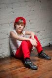 Stående av den kalla unga höftflygturpojken i röd hatt och röda flåsanden Arkivbilder