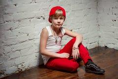 Stående av den kalla unga höftflygturpojken i röd hatt och röda flåsanden Royaltyfri Fotografi