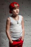 Stående av den kalla unga höftflygturpojken i röd hatt och röda flåsanden Arkivfoto