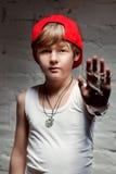 Stående av den kalla unga höftflygturpojken i röd hatt och röda flåsanden Arkivfoton