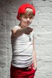 Stående av den kalla unga höftflygturpojken i röd hatt och röda flåsanden Fotografering för Bildbyråer