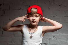 Stående av den kalla unga höftflygturpojken i röd hatt och röda flåsanden Royaltyfria Bilder