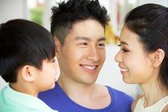 Stående av den kinesiska familjen tillsammans hemma Arkivbild