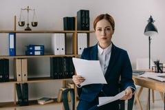 stående av den kvinnliga advokaten i dräkt med dokument i händer på arbetsplatsen royaltyfri fotografi