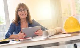 Stående av den kvinnliga arkitekten som arbetar på plan, ljus effekt Fotografering för Bildbyråer