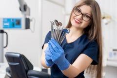 Stående av den kvinnliga attraktiva tandläkaren som rymmer tand- hjälpmedel - på det moderna tand- kontoret Royaltyfri Foto