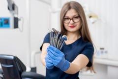 Stående av den kvinnliga attraktiva tandläkaren som rymmer tand- hjälpmedel - på det moderna tand- kontoret Fotografering för Bildbyråer