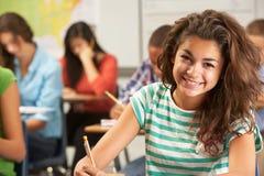 Stående av den kvinnliga eleven som studerar på skrivbordet i klassrum Arkivfoton