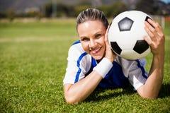 Stående av den kvinnliga fotbollsspelaren som ligger på fotbollfält och innehav en boll royaltyfria bilder