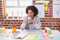 Stående av den kvinnliga inreformgivaren med kaffekoppen på skrivbordet royaltyfri bild