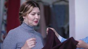 Stående av den kvinnliga klienten som väljer torkduken för klänning lager videofilmer