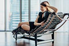 Stående av den kvinnliga modellen som tvärt bär den svarta klänningen och höga häl som kopplar av på stol royaltyfri foto