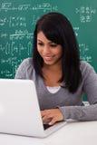 Stående av den kvinnliga studenten som använder bärbara datorn arkivfoto