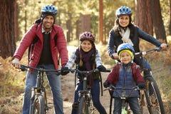 Stående av den latinamerikanska familjen på cyklar i en skog Royaltyfri Fotografi