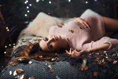 Stående av den ledsna attraktiva unga kvinnan med glitterkonfettier och girlandljus som firar mörkt rum för alonein ` S för nytt  arkivbild