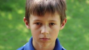Stående av den ledsna unga Caucasian pojken som ser kameran lager videofilmer