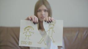 Stående av den ledsna unga kvinnan som ifrån varandra river barns teckning med bilden av mamman och farsan Problem i f?rh?llandet arkivfilmer