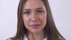 Stående av den ledsna unga kvinnan som tätt gråter upp på vit bakgrund i studio Revakörningar ner kind stock video