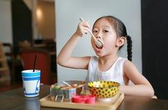 Stående av den lilla asiatiska barnflickan som har frukosten på morgonen royaltyfria bilder