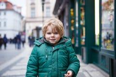 Stående av den lilla litet barnpojken som går till och med staden på förkylning Arkivfoton