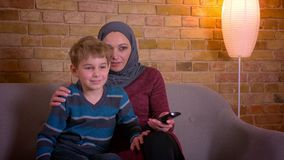 Stående av den lilla pojken och hans muslim moder i hållande ögonen på TV för hijab som tillsammans hemma sitter på soffan lager videofilmer