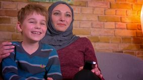 Stående av den lilla pojken och hans muslim modern i hijabbristning som ut hemma skrattar hållande ögonen på komedi på TV lager videofilmer
