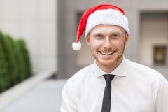 Stående av den ljust rödbrun affärsmannen för framgång på den santa hatten Se kameran och toothy leende Arkivbild