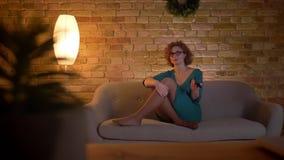 Stående av den ljust rödbrun lockig-haired caucasian flickan i exponeringsglas som håller ögonen på TV med positiv munterhet och  stock video
