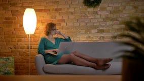 Stående av den ljust rödbrun lockig-haired caucasian flickan i exponeringsglas som ligger på soffan och hänsynsfullt arbetar med  lager videofilmer