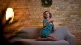 Stående av den ljust rödbrun lockig-haired caucasian flickan som gör selfie-foto genom att använda smartphonen på mysig hem- bakg arkivfilmer