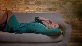 Stående av den ljust rödbrun lockig-haired caucasian flickan som ligger på soffan och gärna talar på smartphonen på mysig hem- ba arkivfilmer