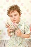 Stående av den lockiga brunögda pojken i en ljus beige klänning Arkivfoto