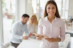 Stående av den lyckade affärskvinnan som rymmer den digitala minnestavlan arkivfoto