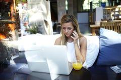 Stående av den lyckade affärskvinnan som talar på mobiltelefonen, medan sitta den öppna bärbar datordatoren för framdel i modernt fotografering för bildbyråer