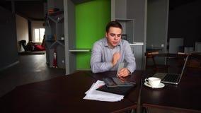 Stående av den lyckade unga manliga affärsmannen som som bort poserar och ser med smartphonen i hand och sitter på skrivbordet stock video