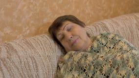 Stående av den lyckliga äldre kvinnan Hon vilar på soffan lager videofilmer