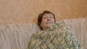 Stående av den lyckliga äldre kvinnan Hon vilar på soffan stock video