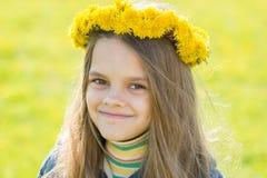 Stående av den lyckliga åtta-år-gamla flickan med en krans av maskrosor på hennes huvud, mot bakgrunden av en vårröjning fotografering för bildbyråer