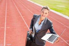 Stående av den lyckliga affärskvinnan som är klar att köra med en bärbar dator och en portfölj arkivbild