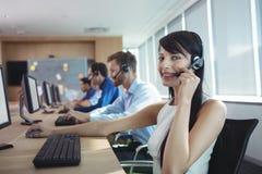 Stående av den lyckliga affärskvinnan som använder hörlurar med mikrofon Fotografering för Bildbyråer