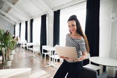 Stående av den lyckliga affärskvinnan som ler för kamera, medan arbeta på inre eller kafét för bärbar datordator i regeringsställ Royaltyfri Fotografi