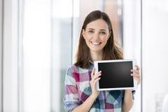 Stående av den lyckliga affärskvinnan som visar den tomma skärmen av den digitala minnestavlan royaltyfri fotografi