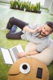 Stående av den lyckliga affärsmannen som använder bärbara datorn och mobiltelefonen på det idérika kontoret Royaltyfria Foton