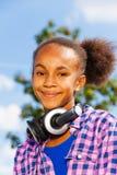Stående av den lyckliga afrikanska flickan med hörlurar Royaltyfri Bild