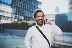 Stående av den lyckliga amerikanska afrikanska mannen som använder smartphonen för att kalla hans vänner på den soliga staden Beg Royaltyfri Fotografi