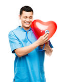 Stående av den lyckliga asiatiska doktorn som lyssnar till hjärtslaget  Arkivfoton