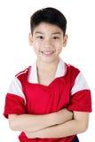 Stående av den lyckliga asiatiska gulliga pojken i röd sportlikformig Arkivfoton